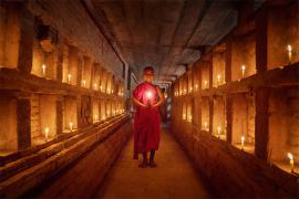 Buddhist monk standing in the middle of a corridor lit with candles
