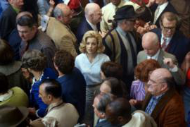 Image of a woman's worried face in a crowd.