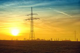 A pair of electrical towers at sunset
