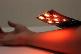 A thin, flexible electronic board, lit-up with red and infrared lights, and approximately three inches wide by three inches wide, is held above a person's forearm.