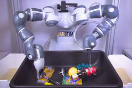 A grey robot with a suction gripper on one arm and a claw gripper on the other is poised above a container of objects.