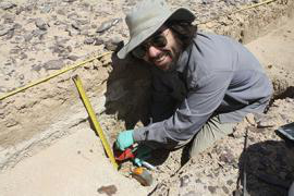 an image of aj white examining an archaeological dig