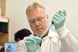 Anders Naar holds a pipette and test tub in a lab