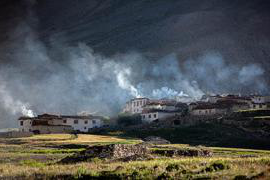 Photo shows houses on a hillside with smoke emerging from smokestacks