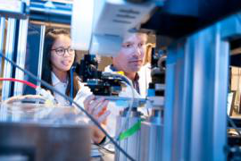 Two students stand behind some scientific equipment
