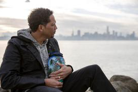 Richard Livingston Jr., whose son Richard Dejion Livingston III was murdered in 2015, sits outside cradling the urn that contains his son's remains. The sky is wintry and cool, and the skyline of San Francisco is in the background. (UC Berkeley photo by Brittany Hosea-Small)