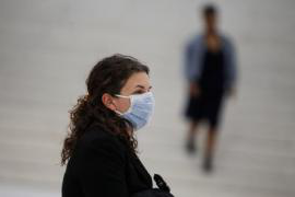 A woman stands on a street wearing a light blue surgical mask.