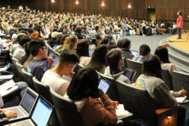 A photo of a large auditorium filled with students all listening to a single speaker on stage.