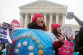A woman wears a birth control pill costume amid a sea of protesters as she protests in front of the Supreme Court in Washington D.C..
