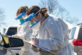 Two National Guard health officers stand outside next to a car wearing personal protective suits and face shields, and writing on clipboards