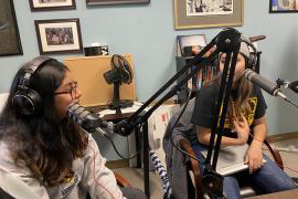 Two students wearing headphones and using recording equipment create a podcast in a recent Chicano Studies class.