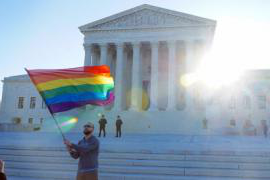 a man waves a rainbow flag in front of the supreme court building