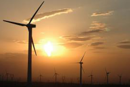 wind turbines silhouetted by sunset