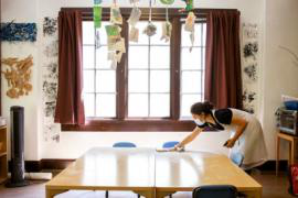 A staff member at Rockridge Little School in Oakland, California, uses a quiet moment to disinfect tables used by preschool students.