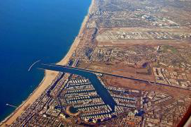 An aerial photo of a coastline showing a bright blue ocean and a developed urban area