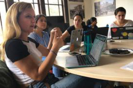 Students in the Human Rights Center Investigations Lab sit at a round table with their laptops and discuss their work.
