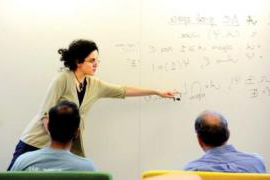 woman discussing math in front of whiteboard, two men looking on